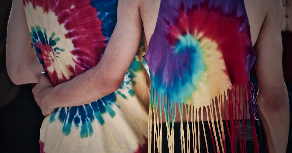 Two people with their backs faced to the picture, wearing tie-dye shirts