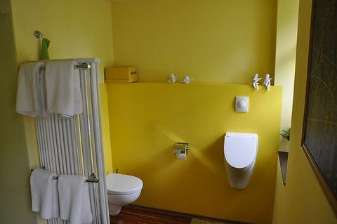 WC und Urinal verstecken sich in einer Nische des Badezimmers hinter dem raumteilenden Heizkörper