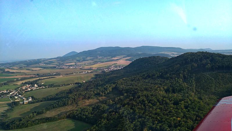 Prelet nad hrebeňom Kapušianskeho hradného vrchu otvára pohľad na obec Fulianku, na konci doliny, ktorej pokračovaním je dlhý hrebeň Slanských vrchov...