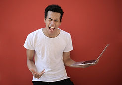 young-ethnic-male-with-laptop-screaming-