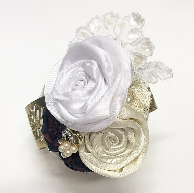 A meaningful corsage handmade from a father's red and blue silk tie, the cream under-portion of the tie, and his daughter's lace Bat Mitzvah suit from the early 90's. The lace appliqué and lace rose is also from his other daughter's Bat Mitzvah.  The corsage is fitted to a gold filagreed cuff bracelet, with a single vintage earring sitting on top of the roses.