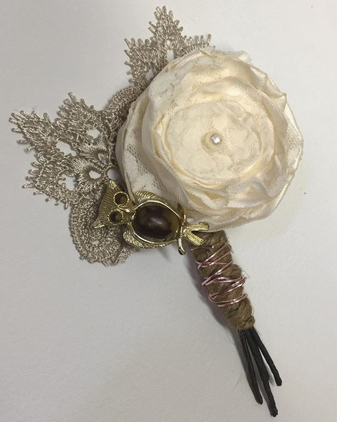 A groom's boutonniere made from a vintage owl pin and vintage piece of lace.