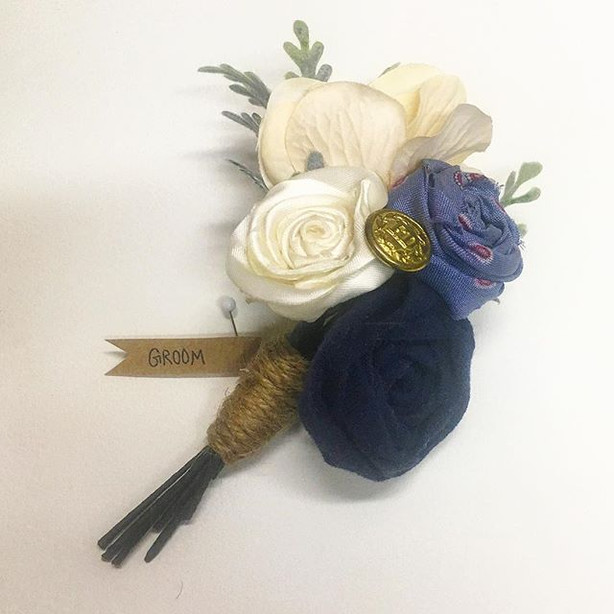 A grooms boutonniere made from the bride's late Father's blue and marron tie, the groom's dark blue FDNY t-shirt, and his FDNY pin.