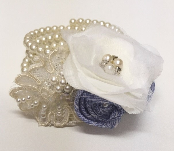 A Mother of the Bride's corsage sewn onto a pearl bracelet.   The flowers are made from the Bride's Mother's 1970's wedding dress, her Grandmother's earring, and her late Grandfather's blue button down MTA shirts.