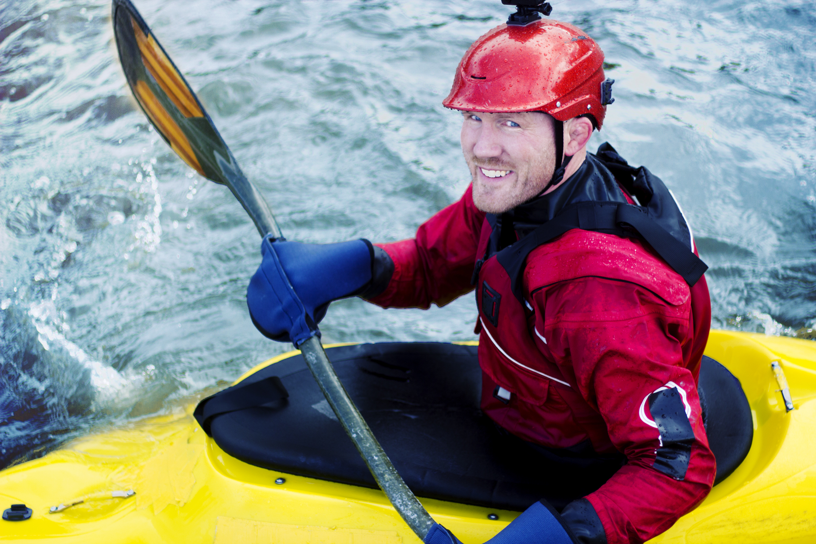 A Kayaker Smiling As He Goes Down a River