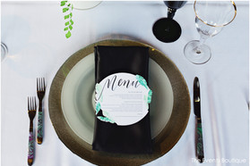 tropical wedding with black place setting with gold rimmed glass