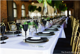 tropical wedding with black place setting with gold rimmed glass and gold chairs