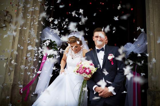 wyjście-młodej-pary-z-kościoła.jpg Para młoda uśmiechnięta wychodzi z kościoła. Zostaje obsypana confetti w postaci białych motylków. Panna młoda ubrana w białą suknię ślubną trzyma się za sukienkę oraz trzyma biało-różowy bukiet ślubny. Pan młody składając razem ręce ubrany jest w ciemny garnitur z czarną muchą.