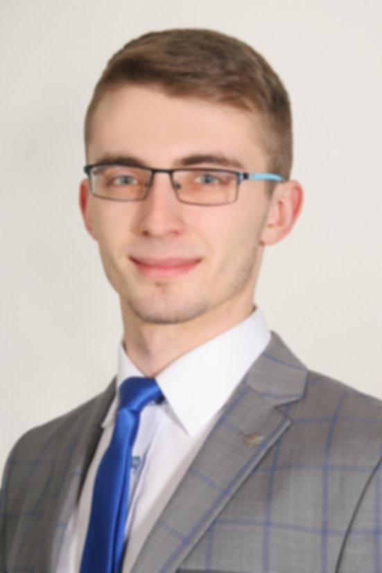 Portret-Piotr.jpg Zdjęcie mężczyzny o włosach koloru ciemny blond, noszącego biebieskie okulary, ubranego w szary garnitur w niebieską kratę, białą koszulę oraz ciemno-niebieski krawat.