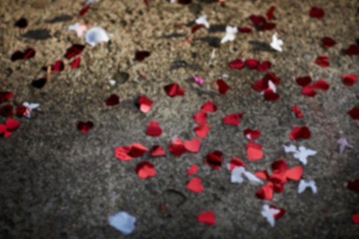confetti-serce.jpg Położone na ziemi confetti w postaci małych czerwonych serduszek oraz białych motylków.