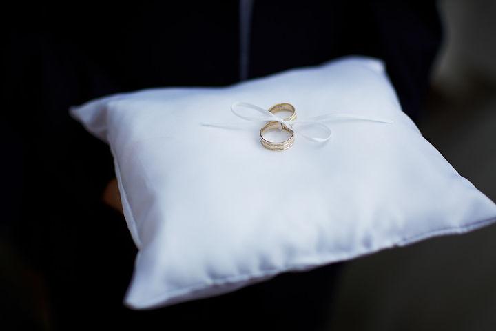 obrączki-na-poduszce.jpg 2 złote obrączki ślubne przywiązane białą, cienką kokardką do białej poduszki.