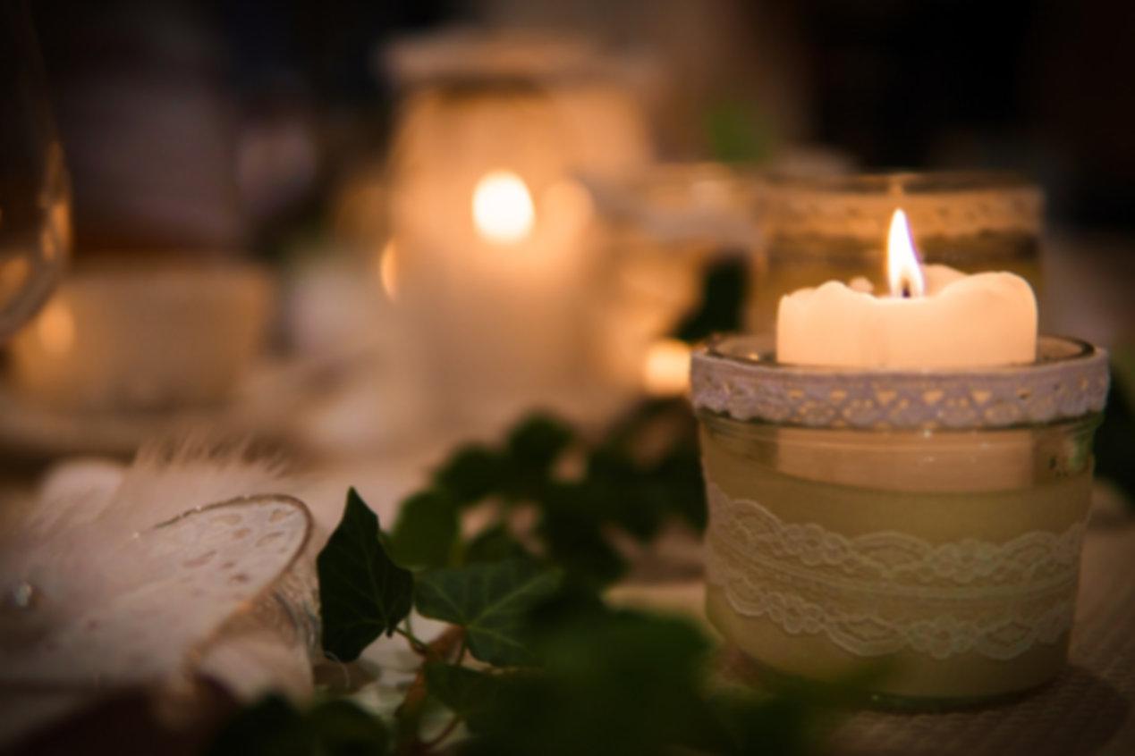 świeczka-concierge.jpg Na stole po prawej stronie znajduje się zapalona świeczka, na środku kawałek zielonego bluszczu, a po lewej stronie biała ozdoba. W oddali rozmazana zapalona świeca.