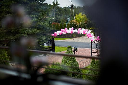 dekoracje-balony.jpg Ozdoba bramy wjazdowej do posesji w postaci złączonych nad otwartą czarną bramą białych i różowych balonów. Widok z okna mieszkania.