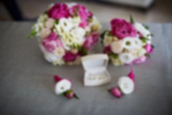 obrączki-bukiet-ślubny.jpg 4 dekoracje kwiatowe na rękę 2 duże i 2 małe a pośrodku nich 2 złote obrączki ślubne ułożone w białym pudełku.
