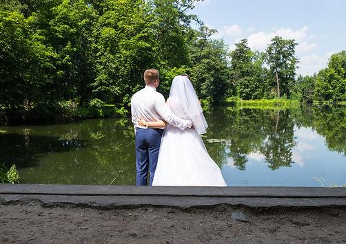 para-młoda-nad-wodą.jpg Obejmująca się para młoda odwrócona tyłem spogląda na rzekę oraz zielone drzewa na brzegu. Panna młoda po prawej stronie ubrana w białą ślubną suknię i welon, pan młody w białej koszuli i niebieskich spodniach po lewej stronie.
