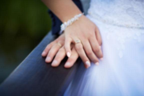 miłość-dłonie-złączone-na-zawsze.jpg dwie dłonie kobiety ubranej w białą suknię i mężczyzny położone na sobie na drewnianej poręczy. Dłonie posiadają złote obrączki ślubne, a dłoń kobiety ma dodatkowo białą bransoletkę z małych kwiatków.