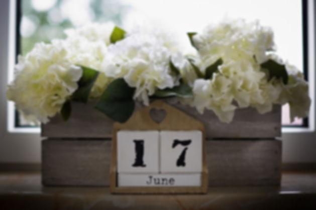 dekoracje-z-białych-kwiatów.jpg Białe kwiaty włożone do drewnianej skrzynki położonej na parapecie przed oknem. Skrzynka z napisem 17 June i małym serduszkiem.