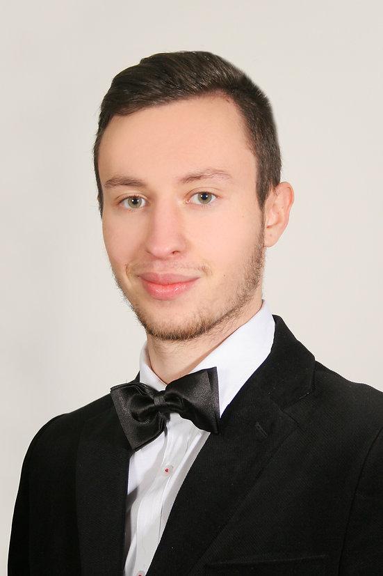 Wizerunek-Piotr.jpg Portret mężczyzny bruneta z czarnym zarostem, ubranego w czarny garnitur, białą koszulę oraz czarną muchę do garnituru.