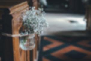kwiaty-w-wazonie.jpg Białe małe kwiatki włożone do przezroczystego wazonu z wodą wiszącego na drewnianej ściance w kościele.