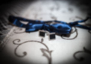 muszka-ślubna-spinki-do-koszuli.jpg 2 czarno-srebrne spinki do mankietów ułożone na białym ozdobnym obrusie przed niebieską, rozłożoną muchą do garnituru.