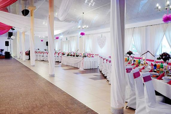 sala-weselna-ułożenie stołów.jpg Sala weselna z trzema stołami weselnymi oraz krzesłami. Wszystkie stoły i krzesła okryte białymi narzutami. Na stołach porozstawiane jedzenie i picie. Cała sala ozdobiona białymi ozdobami.