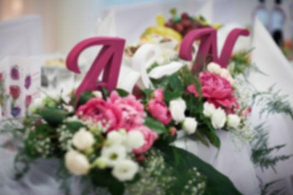 """stół-młodej-pary-dekoracje.jpg Dekoracje na stole w postaci 2 liter, iniciałów ,,A"""" i ,,N"""" w kolorze bordowym ułożone na kwiatkach koloru białego i różowego."""