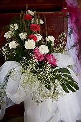 dekoracje-kościoła-bukiet.jpg Bukiet składający się z gerberów w kolorze białym, czerwonym i różowym, owinięte w białą wstążkę.