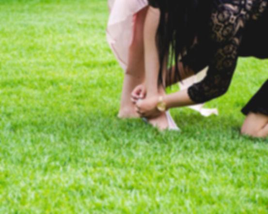 concierge-pomoc-w-nietypowych-sytuacjach.jpg kobieta w czarnej sukience i złotym zegarku klęcząc na zielonej trawie zawiązuje wstążkę na gołej stopie dziewczynki.