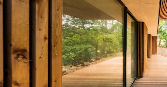 Vue filante sur les baies vitrées d'une villa dans la nature