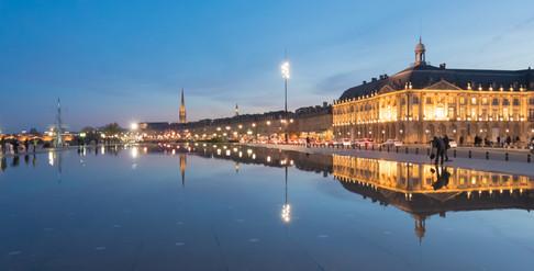Symétrie d'immeubles à Bordeaux entre ciel et eau