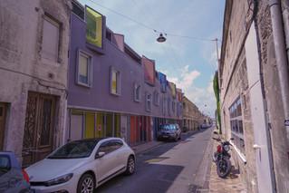 Transition radicale entre les façades traditionnelles et les couleurs vives d'une récente réhabilitation
