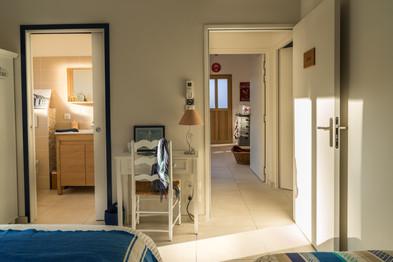 Une chambre avec vue sur la salle d'eau et la porte d'entrée