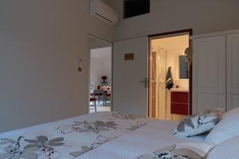 La chambre depuis le lit vue sur le séjour et la salle de bains