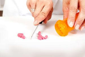 Pharmacist cutting pills