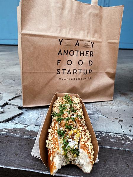 Veganer Hotdog vor Papiertüte mit Organic Garden Stempel