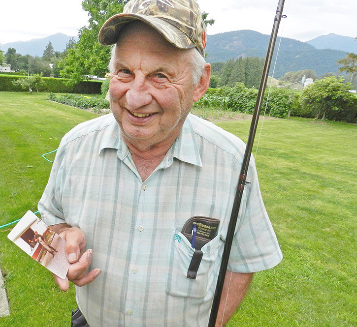 Walter Beutler with a picture of himself holding a 53-pound spring. The long-time Fraser River recreational angler is concerned about the future of the sport. — Image Credit: GREG KNILL Black Press