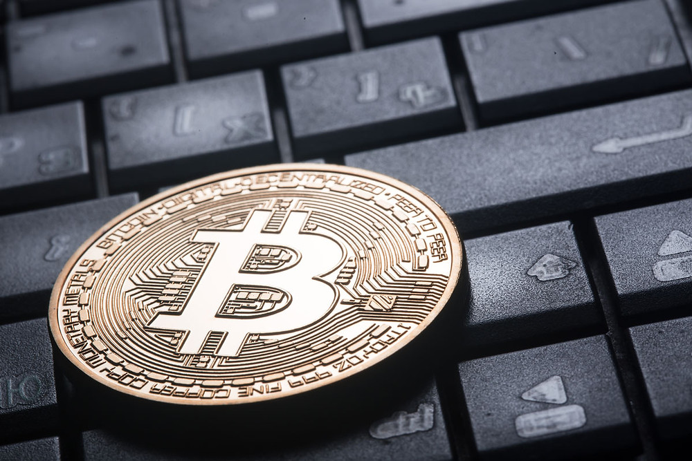 Bitcoin currency on black keyboard
