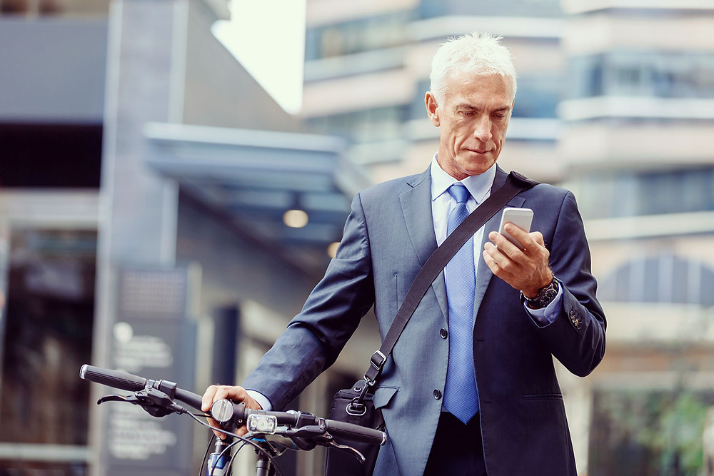businessman in suit and with bicycle looking at smartphone