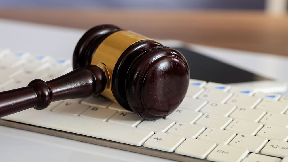 judge's gavel on top of a keyboard near a smartphone