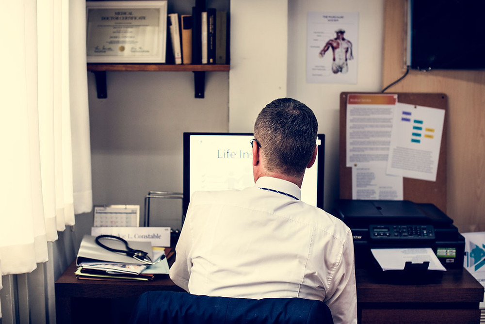 Doctor working on a computer at his desk