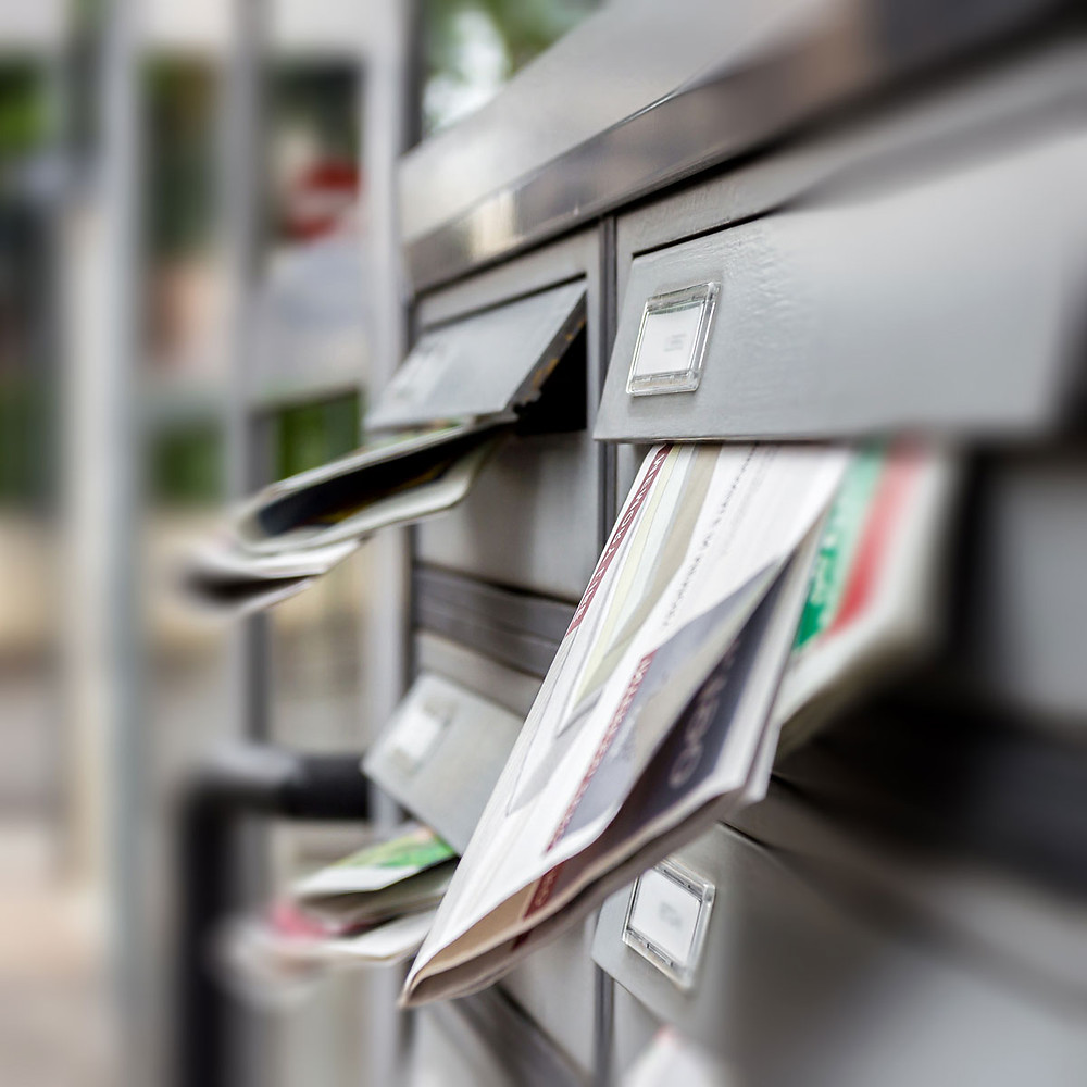 Letters and junk mail overflowing in mailboxes
