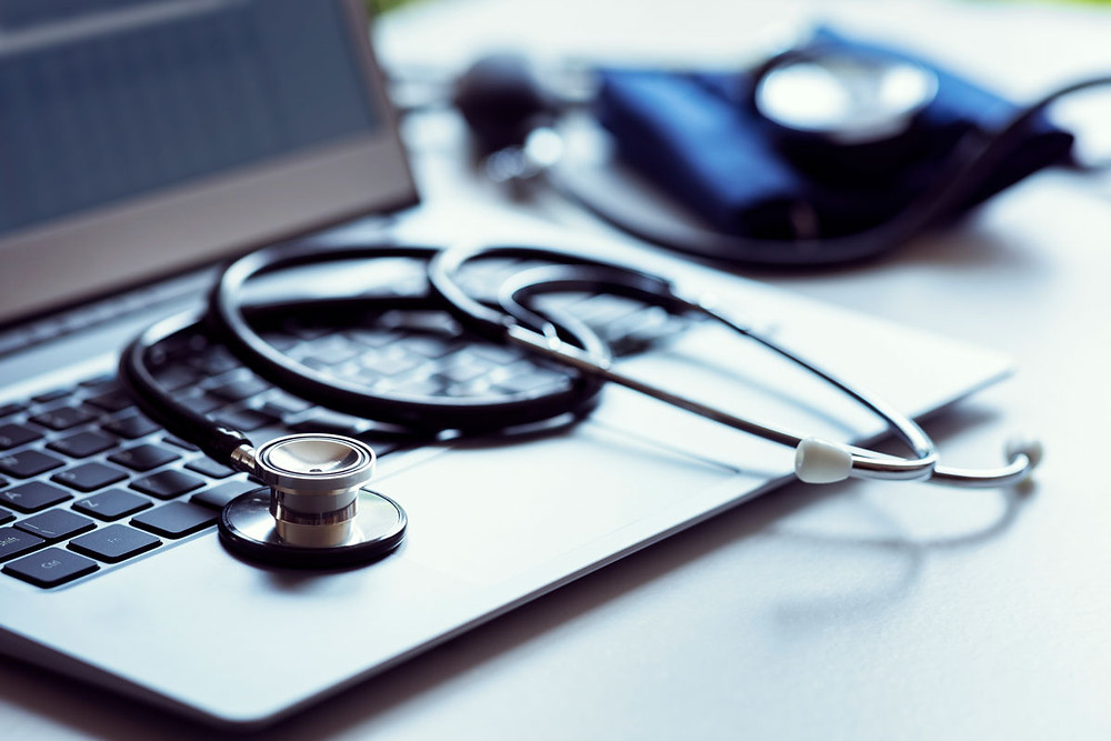 Stethoscope on top computer with blood pressure sleeve on the side