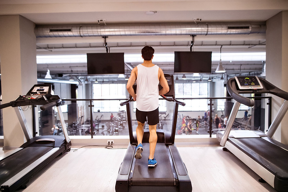 young, fit man running on a treadmill in the gym
