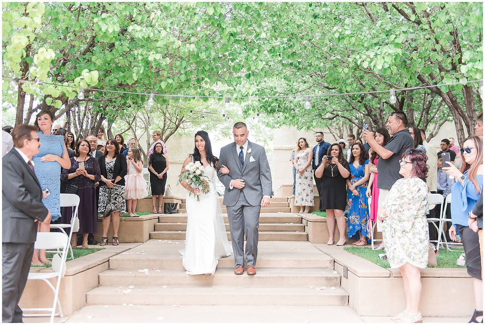 Bride walking down the aisle at outdoor ceremony at Calvary Chapel Albuquerque