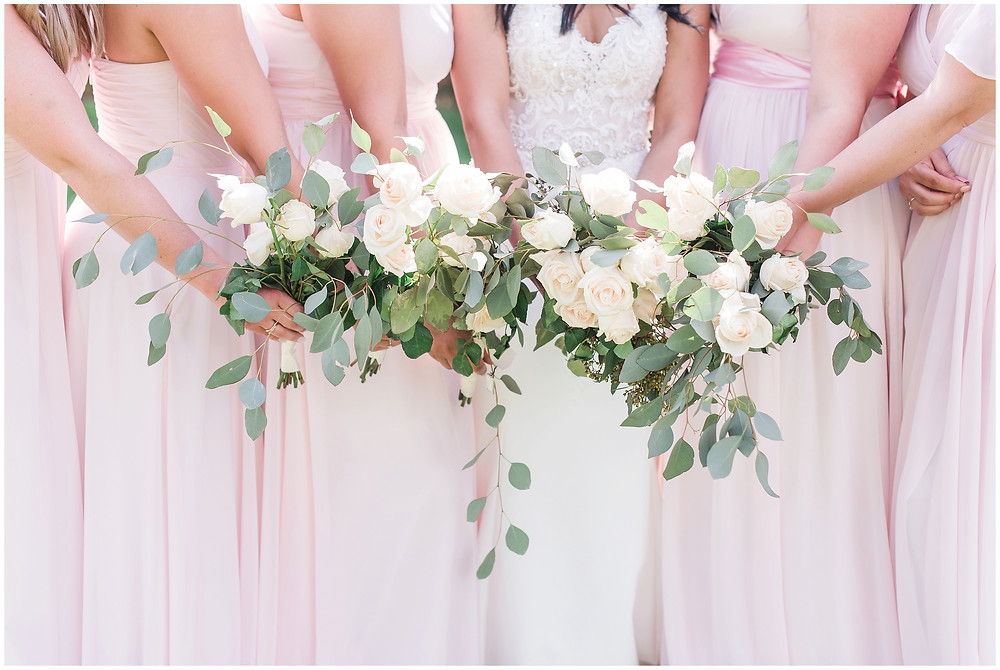 Pink bridesmaids dresses. Bridesmaids holding white rose and eucalyptus bouquets.