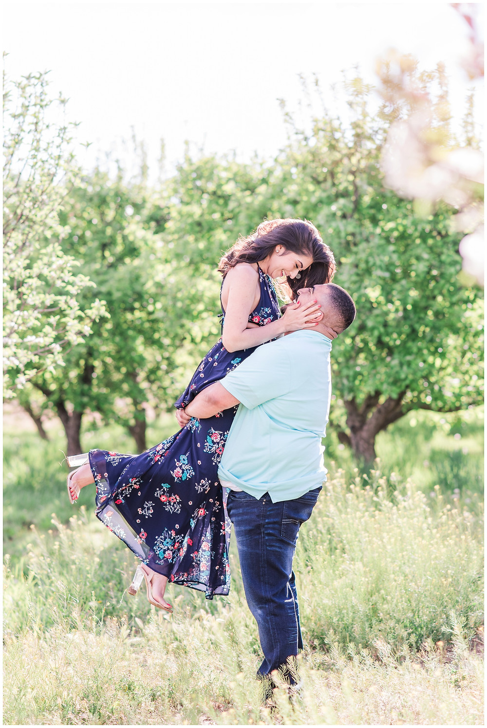 Flower tree engagement in corrales, new Mexico. Albuquerque wedding photographer Maura Jane Photography. Outdoor engagements session in New Mexico. Groom lifting bride in apple orchard in engagement session