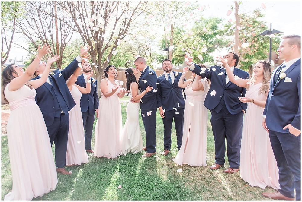 Bride and groom kissing in rose petal toss. Bridal party throwing rose petals at bride and groom.