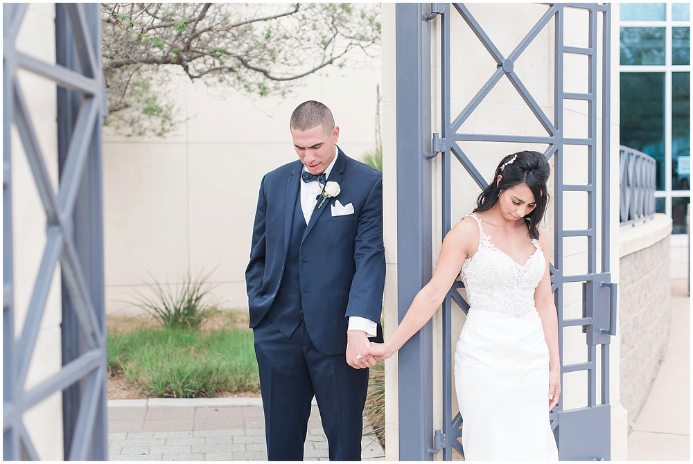 Bride and groom praying before ceremony. Bride and groom holding hands around the corner. Wedding at Calvary Albuquerque