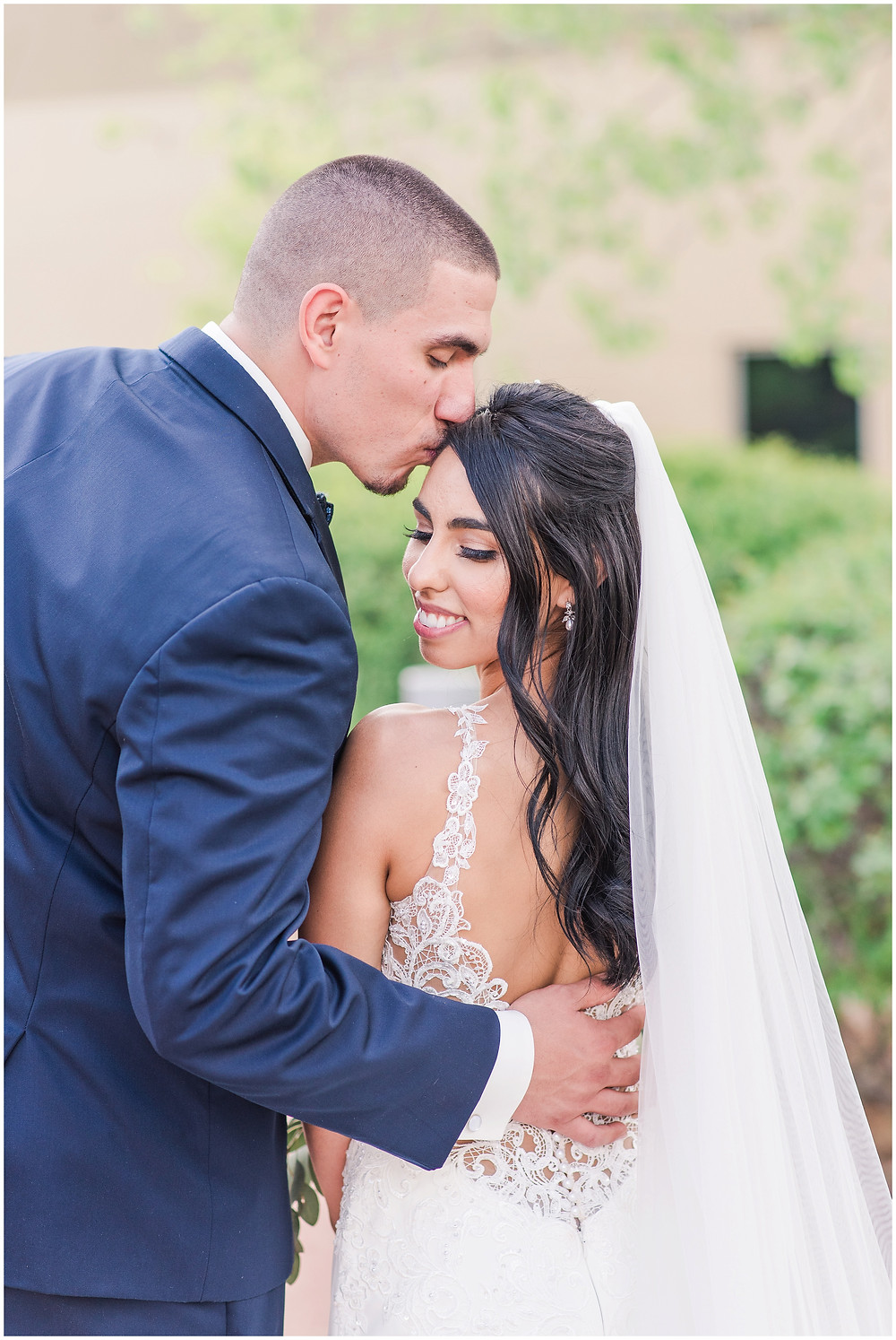 Bride and groom wedding photos. Groom kissing bride in backless lace wedding dress with long veil