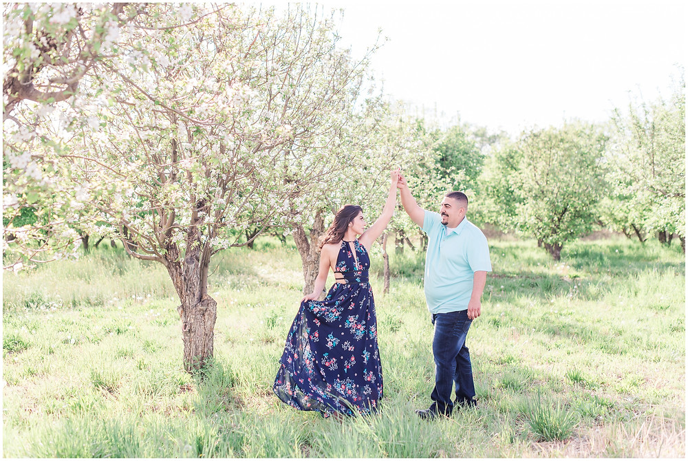 Flower tree engagement in corrales, new Mexico. Albuquerque wedding photographer Maura Jane Photography. Couple dancing in apple orchard in long navy dress